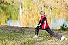 Kobieta robi ćwiczeń sportowych w parku jesienią | Stock Foto