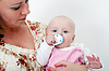 Baby with pacifier in arms of mother | Stock Foto