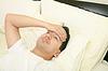 Joven enfermo está acostado en la cama | Foto de stock