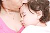 Madre joven encantada cuidando a su bebé | Foto de stock