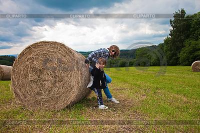 Dziewczyna i chłopak naciska okrągłą wiązkę słomy. | Foto stockowe wysokiej rozdzielczości |ID 3024346