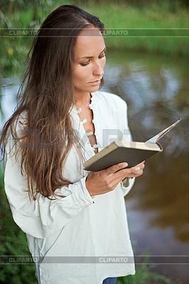 Czytanie młoda kobieta w pobliżu rzeki | Foto stockowe wysokiej rozdzielczości |ID 3016800
