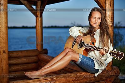 Młoda kobieta, grając na gitarze w altance | Foto stockowe wysokiej rozdzielczości |ID 3017248