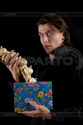 Erstaunter Vampir hält Geschenkbox mit Knoblauch | Foto mit hoher Auflösung |ID 3022244