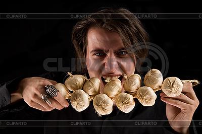 Zło wampirem z scary oczy jedzenia czosnku | Foto stockowe wysokiej rozdzielczości |ID 3022253