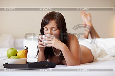 Młoda piękna kobieta picia kawy leżącego na białym łóżku | Foto stockowe wysokiej rozdzielczości |ID 3024301