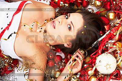 Piękna brunetka leżącego wśród dekoracji świątecznej | Foto stockowe wysokiej rozdzielczości |ID 3032444