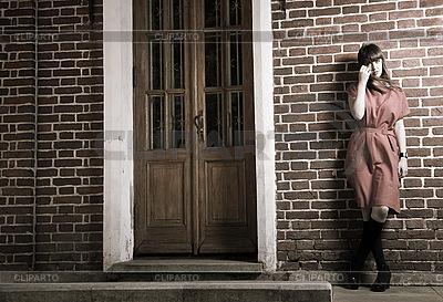 Piękna młoda kobieta przed murem | Foto stockowe wysokiej rozdzielczości |ID 3104799