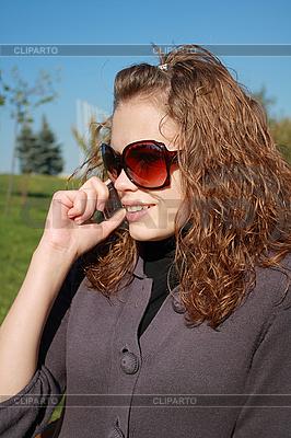 Dziewczyna w wielkich okularach mówi przez telefon | Foto stockowe wysokiej rozdzielczości |ID 3047511