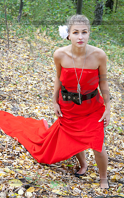 Ładna dziewczyna w czerwonej sukni w lesie | Foto stockowe wysokiej rozdzielczości |ID 3092858