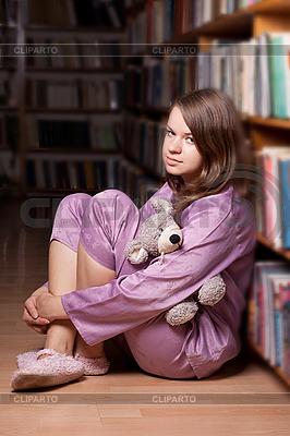 Dziewczyna w różowej piżamie w bibliotece | Foto stockowe wysokiej rozdzielczości |ID 3092890