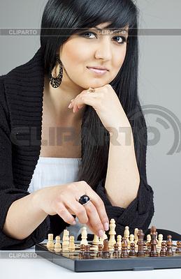 Eine schöne junge Frau, brünett spielt Schach zu Hause | Foto mit hoher Auflösung |ID 3239415