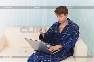 Guy arbeitet im Internet auf dem Sofa und trinkt Kaffee | Foto mit hoher Auflösung |ID 3159778
