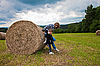 Photo 300 DPI: girl and boy pushing round bundle of straw.