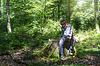 年轻的男孩用小刀以削减棒,而外出 | 免版税照片