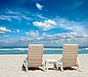两个太阳沙滩椅上岸边近洋 | 免版税照片