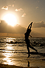 Girl jumping on sunrise at the beach | Stock Foto