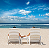 Couple in beach chairs holding hands near ocean | Stock Foto