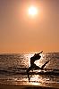 Female jumping at beach on sunrise | Stock Foto