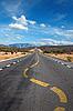 扭在沙漠道路上的车道标志 | 免版税照片