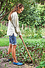 Young woman with hoe in garden | Stock Foto