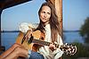 Mujer joven que toca la guitarra | Foto de stock