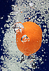 Orange (mandarin) falling in water with air bubbles | Stock Foto