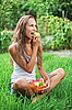 Photo 300 DPI: Beautiful woman eating pear on the green grass