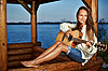 Young woman playing guitar in summerhouse | Stock Foto