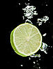 Lime (lemon) falling in water on black | Stock Foto