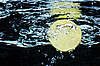 Slice of lime (lemon) falling in water with air bubbles | Stock Foto