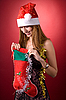 Photo 300 DPI: Smiling girl looking into Christmas stocking