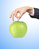 Woman hand with fresh green apple over blue | Stock Foto