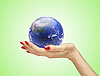 Hand with the world globe over green | Stock Foto