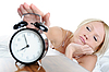 Sleepy woman turns off the alarm | Stock Foto