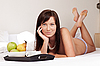 Young beautiful woman having breakfast lying on white bed  | Stock Foto