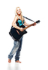 Teenage girl playing an acoustic guitar wearing jeans | Stock Foto