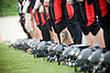 Row of football helmets and feet   Stock Foto