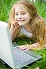 微笑的小女孩,笔记本电脑 | 免版税照片