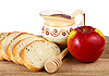 Honey in jug, bread and apple on breadboard | Stock Foto