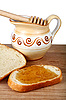 Honey in jug and loaf on breadboard | Stock Foto