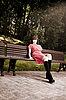 美丽的女人坐在公园的长椅   免版税照片