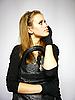 Mujer joven en traje con guantes negros | Foto de stock