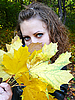 Photo 300 DPI: brown-haired woman holds yellow leaves in hand