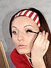 Mädchen malt die Wimpern mit einem Pinsel | Stock Foto
