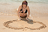 Beautiful girl painting heart on the sand | Stock Foto