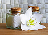 Bottles of sea salt and oil with white flower | Stock Foto