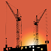 Silhouettes of construction cranes and buildings