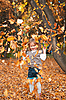 Little girl playing with autumn leaves | Stock Foto