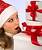 Young girl in Christmas hat with gifts | Stock Foto